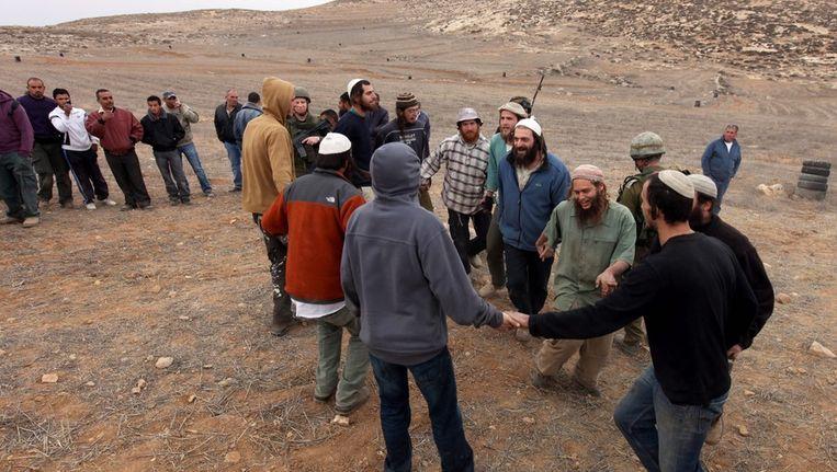 Joodse kolonisten zingen en dansen op Palestijns grondgebied, bij de stad Yatta op de Westoever, nadat ze Palestijnse boeren hebben verjaagd, eind 2010. Beeld EPA