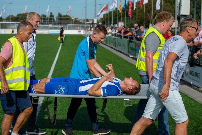Gert-Jan van Leiden verlaat op een brancard het veld nadat zijn rechterschouder tijdens het duel met Ter Leede uit de kom is geschoten.