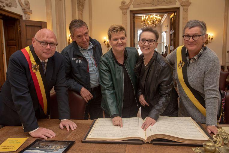 Bieke (tweede van rechts) met schepen De Gelder, burgemeester Alain Pardaen, Hugo Verraes en Biekes zuster Lilliane bekijken het geboorteregister van 1968.