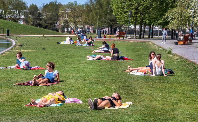 Jongeren liggen te zonnen in het Griftpark in Utrecht. Beeld Raymond Rutting / de Volkskrant