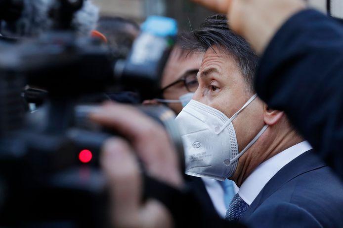 Premier Giuseppe Conte wordt belaagd door verslaggevers bij het verlaten van het regeringsgebouw in Rome.