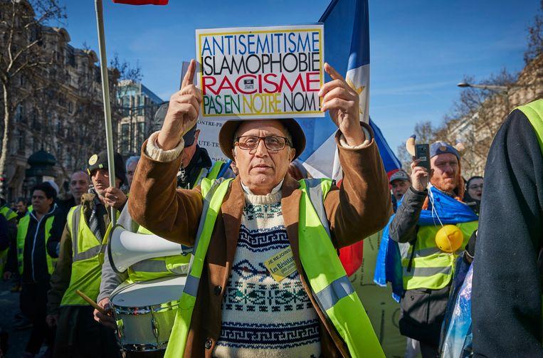 Een man met een geel hesje houdt in Parijs een plakkaat op met het opschrift 'antisemitisme, islamofobie en racisme, niet in onze naam'. Beeld Getty Images