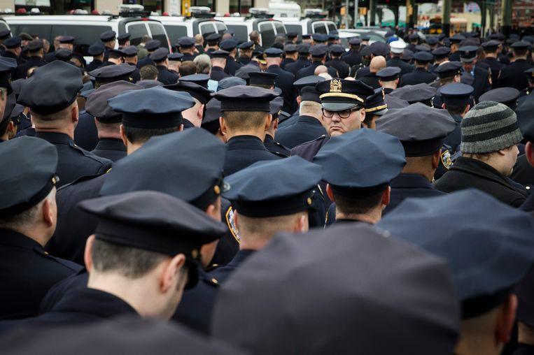 Agenten keren hun rug naar burgemeester Bill de Blasio tijdens een herdenkingsceremonie vandaag in New York. Beeld AP