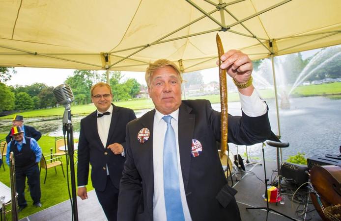 'Boris Johnson' (Henk Blom) presenteert wethouder Sandmann (l) een 'gemanipuleerde haring'.