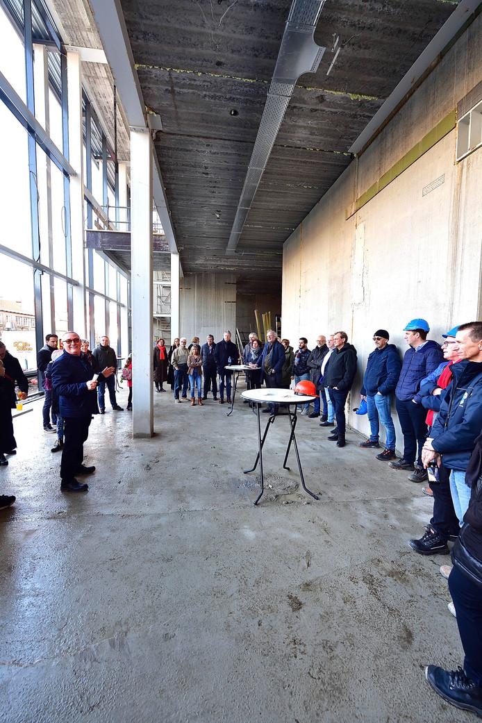 Carlo Lambregts(l) spreekt de bouwvakkers en de bewoners toe.