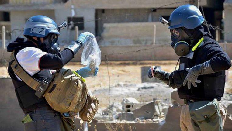 Leden van een onderzoeksteam naar chemische wapen verzamelen monsters van mogelijk chemische raketten in Syrië. Beeld ap
