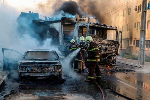 De brandweer blust een uitgebrande auto in Fortaleza.