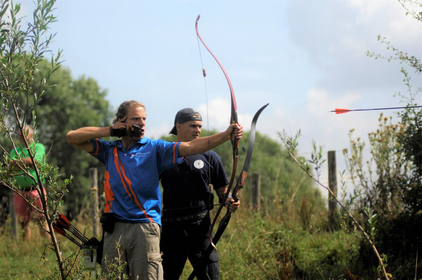 Thijs Bezemer (l) vuurt een pijl af tijdens het EKField Archery bij Kasteel Doorwerth.