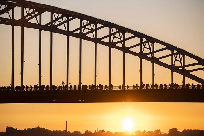 Deelnemers wandelen over de Waalbrug op de eerste dag van de honderdste editie van de Nijmeegse Vierdaagse . De eerste wandeldag heet traditiegetrouw de Dag van Elst. FOTO ANP PIROSCHKA VAN DE WOUW