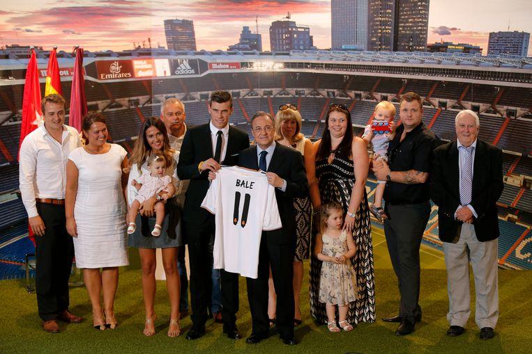 Gareth Bale en zijn familie poseren bij zijn presentatie met het nieuwe Real-shirt en preses Florentino Perez. Beeld AP
