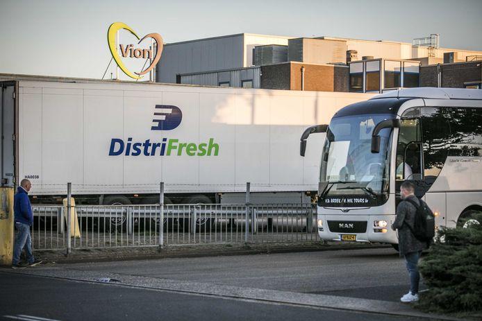 Een touringcar verlaat het terrein van het slachthuis van Vion in Apeldoorn. Vion zet sinds donderdag touringcars in om medewerkers naar het werk te brengen. Het dragen van mondkapjes in de bussen is verplicht.