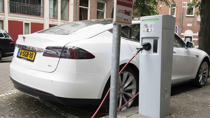 Een Tesla wordt opgeladen aan een laadpaal. In steeds meer steden worden die palen een normaal verschijnsel in het straatbeeld