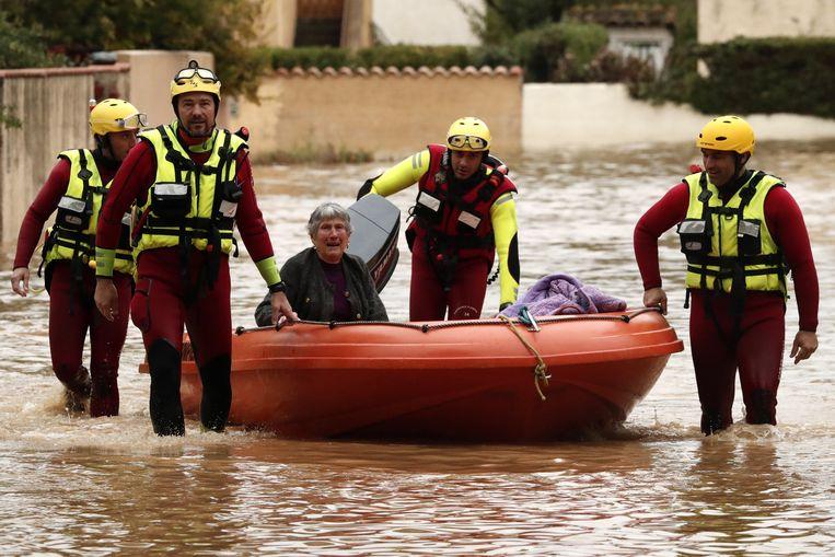 Een oudere vrouw wordt geëvacueerd door brandweermannen in Villeneuve-les-Beziers.