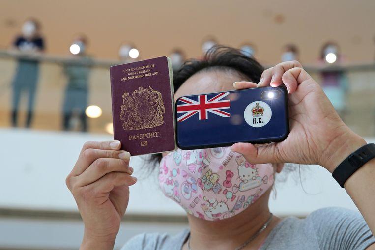 Een demonstrante in Hongkong laat haar Brits overzees paspoort zien. Op de beschermingshoes van haar smartphone staat de voormalige vlag van Honkong, toen  de miljoenenstad nog onderdeel was van de Britse kroon.