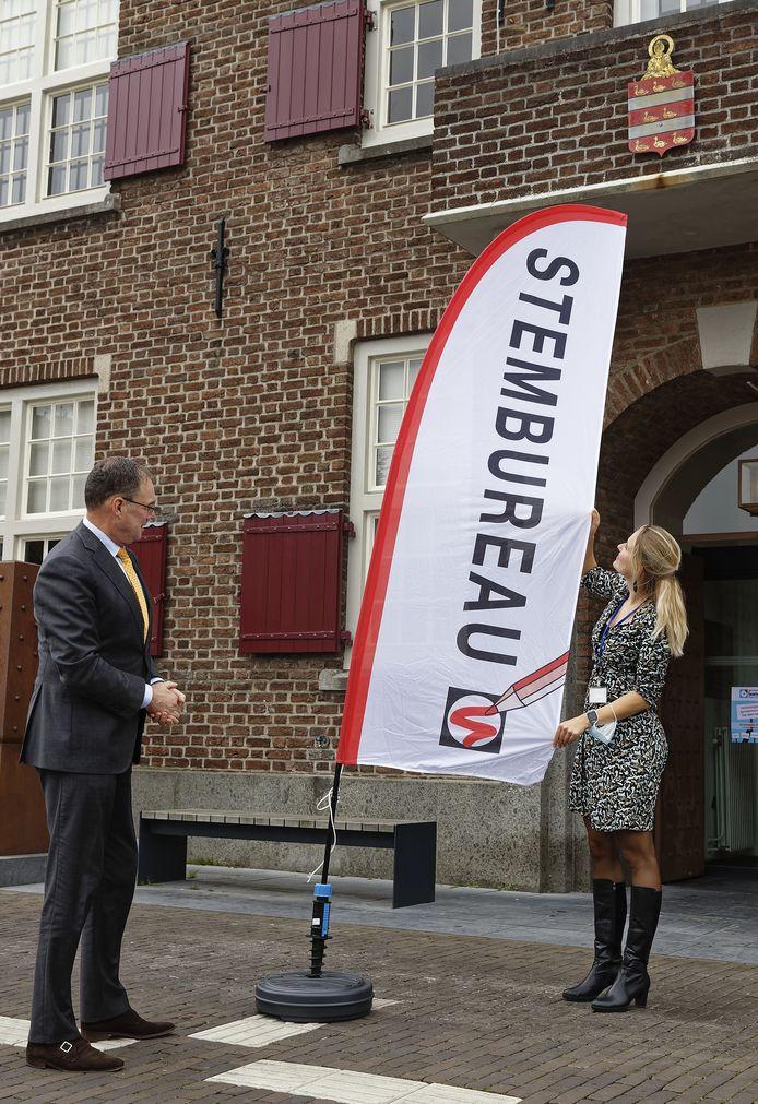Burgemeester Ronald van Meygaarden zet de stemmenvlaggen klaar bij het Boxtelse gemeentehuis.
