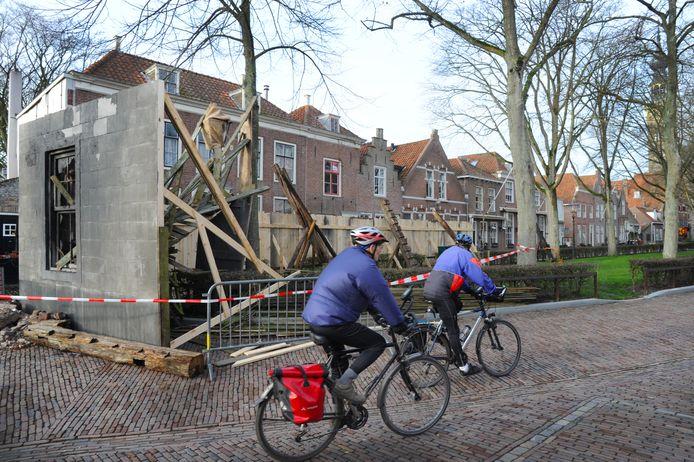 Fietsers passeren een decorstuk voor de Slag om de Schelde.