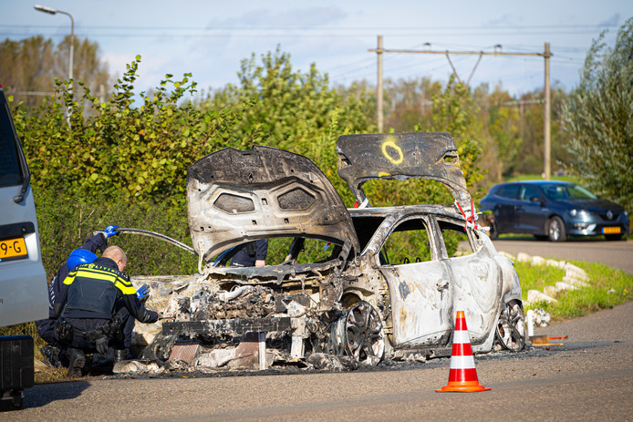 De politie onderzoekt de uitgebrande Renault.