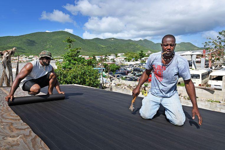 Twee arbeiders leggen dakbedekking op een huis dat door orkaan Irma zwaar is beschadigd, 9 december 2017 in Phillipsburg, Sint Maarten. Beeld Guus Dubbelman / de Volkskrant