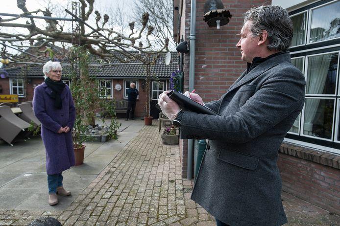Joost van der Zwalm (r) van makelaar Hypodomus zorgt bij het opnemen van een huis voor de verkoop dat hij handschoenen aan heeft en afstand houdt.