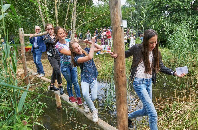 Het aftredende jeugdcollege van Oss neemt de balansbrug over het water in gebruik: Jara van Doorn, Rosa Treebus, Fleur Janssen en Fleur Bak. Achter hen wethouder Kees van Geffen.