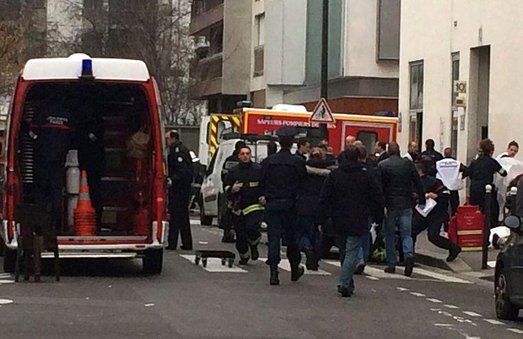 Hulpverleners bij het kantoor van Charlie Hebdo Beeld anp