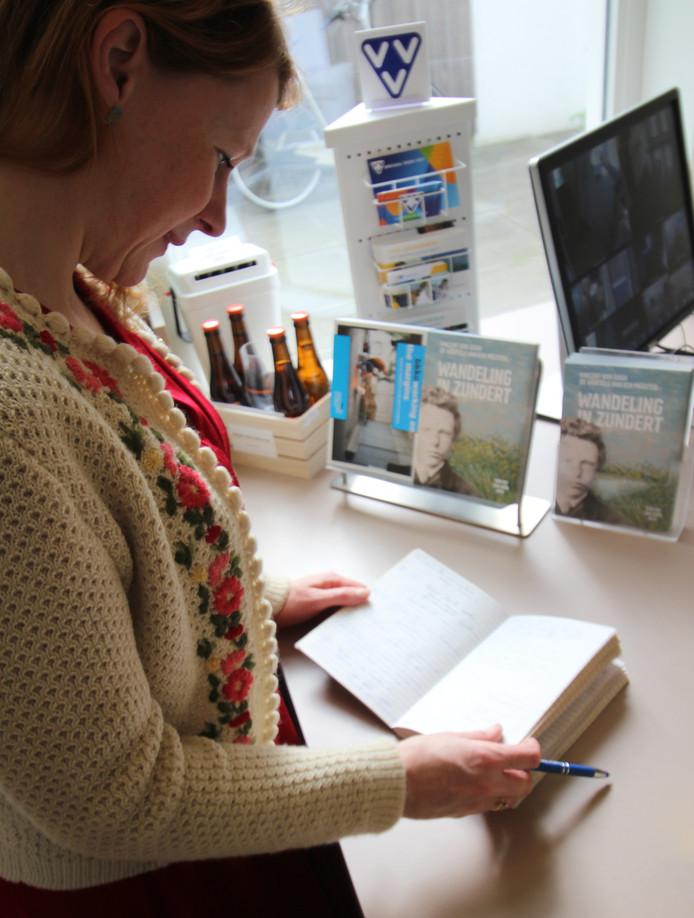 Eva Geene bladert door het boekje van het Van Gogh Huis