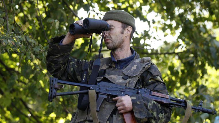 Een Oekraïense militair houdt pro-Russische separatisten bij Donetsk in de gaten. Beeld reuters