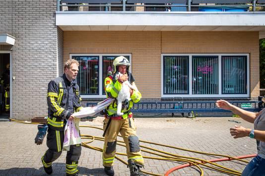 Brandweerlieden redden een kat uit de bedrijfswoning naast het pand van Stella Fietsen in Nunspeet.