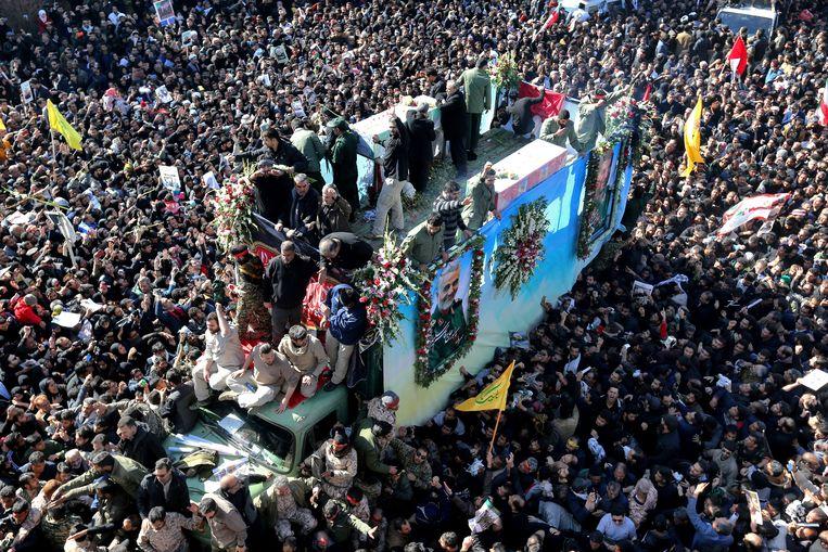 De kist met het lichaam van generaal Qassem Soleimani wordt door Kerman gereden. Een dag eerder trok de begrafenisstoet in Teheran een miljoen bezoekers. Beeld AP