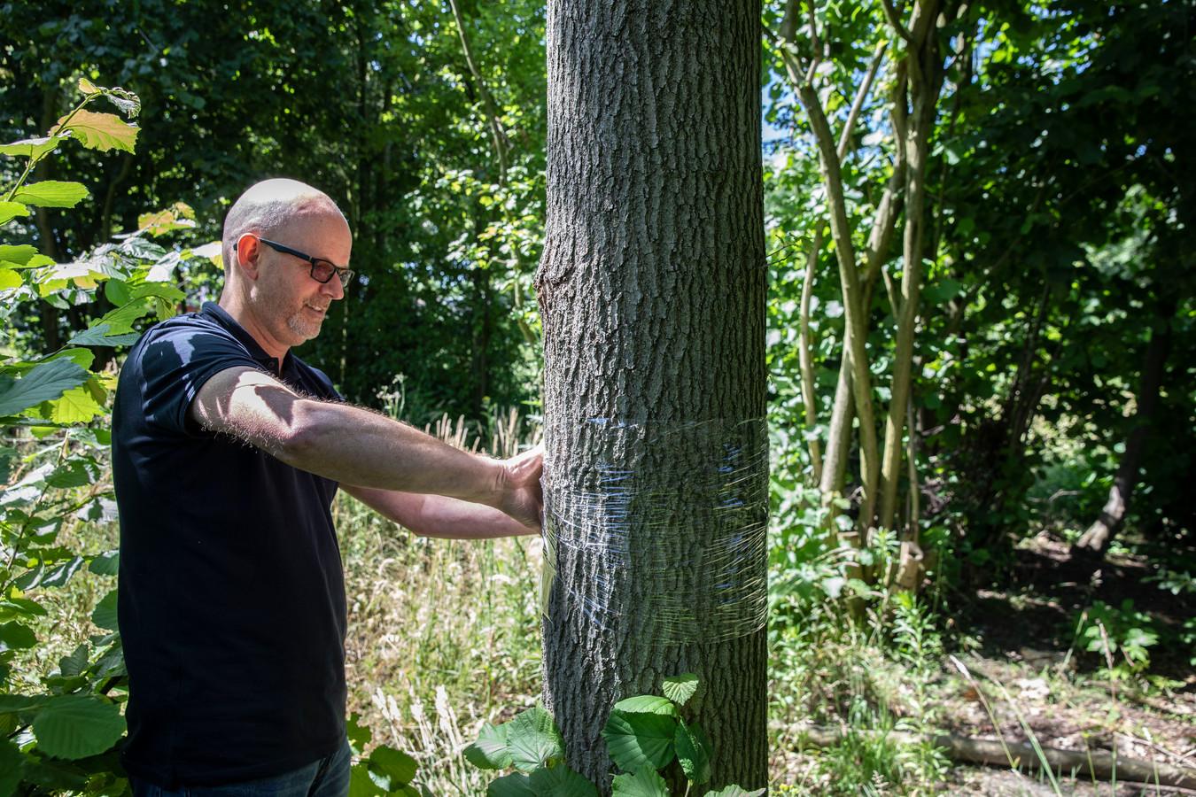 Ruud Obdeijn verpakt bomen en nesten in plastic folie.