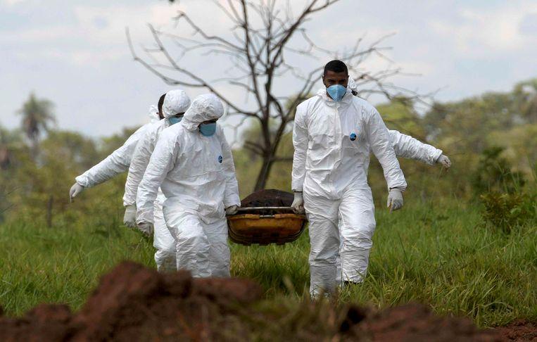 Reddingswerkers dragen een lichaam weg.