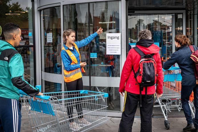 Supermarktmedewerkster Mele van  bij AH XL in Nijmegen, wijst klanten op de nieuwe regels: iedereen een winkelkarretje.