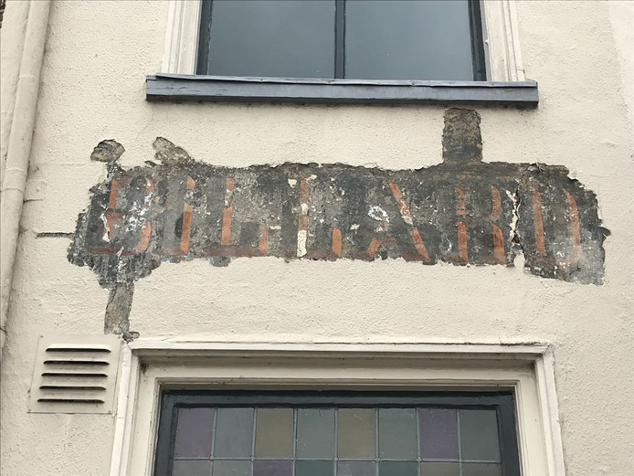 """Na 24 lagen verf te hebben weggekrabd vond kleurhistoricus Bert Jonker de letters Billard op de gevel van café De Tagrijn. ,,Deze moeten er rond 1850 op hebben gestaan"""", aldus de expert."""