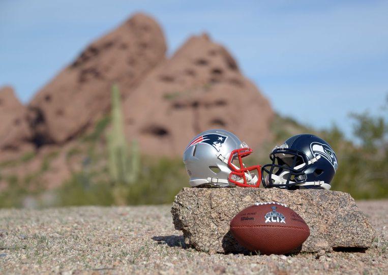 De helmen van de Patriots (links) en Seahawks met een Super Bowl-wedstrijdbal. Beeld reuters