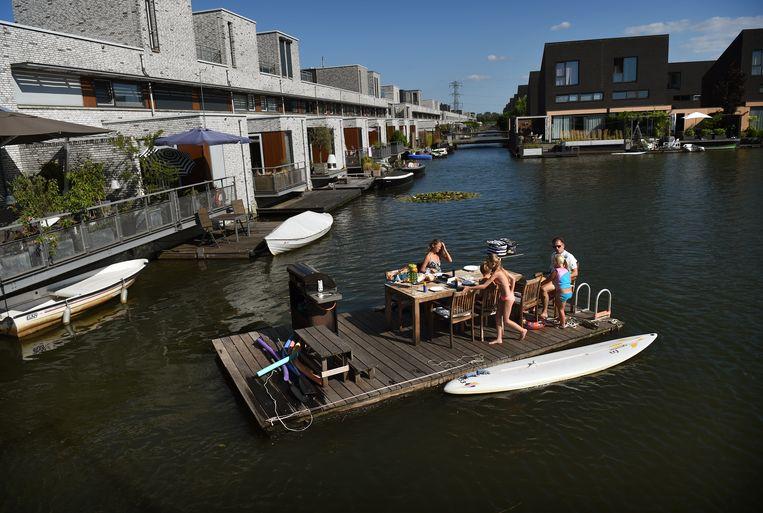 Een gezin viert vakantie in een vinnexwijk in Den Bosch.  Beeld Marcel van den Bergh / Volkskrant