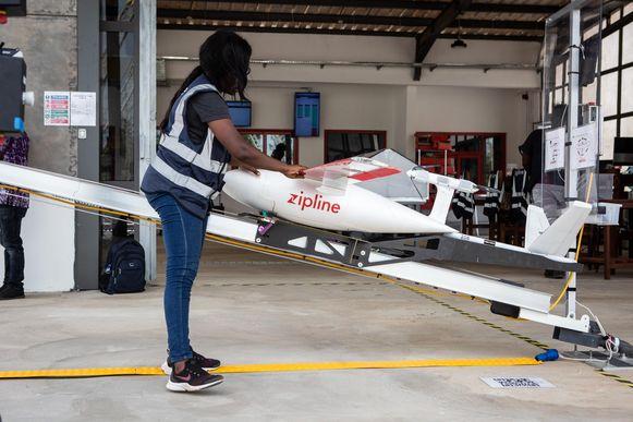Een medewerker laadt een drone voor een levering in Ghana.