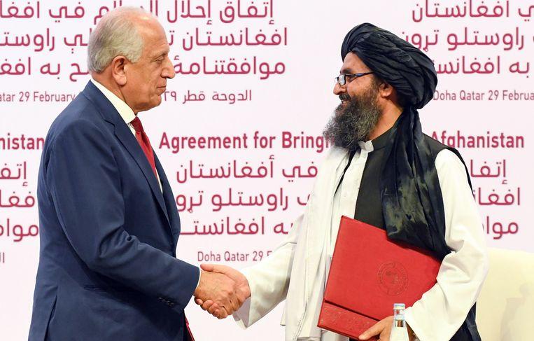 De Amerikaanse speciaal gezant voor Afghanistan (l) en medeoprichter van de Taliban, Mullah Abdul Ghani Baradar, schudden handen tijdens de ondertekeningsceremonie in Doha. Beeld EPA