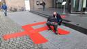 Zelfbenoemd Volkskunstenaar Ralph Posset uit Den Bosch brengt met een assistent een hakenkruis aan als rode loper voor de bezoekers van de tentoonstelling Design van het Derde Rijk bij Design Museum Den Bosch.