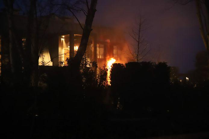 De vlammen schieten uit de woning aan de Platteweg
