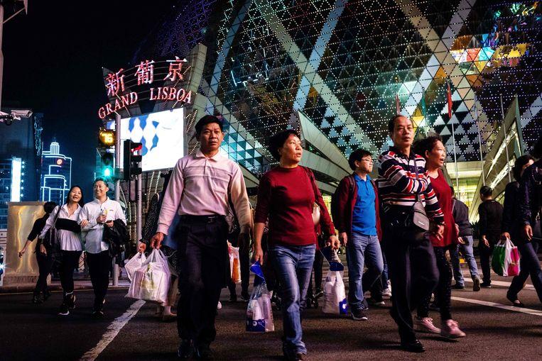 Winkelende toeristen lopen langs het Grand Lisboa Casino in Macau.  Beeld Eduardo Leal / AFP