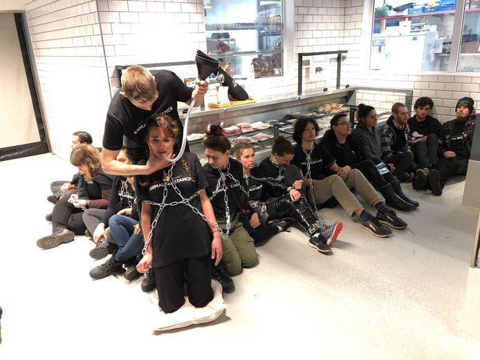 Zo'n vijftien actievoerders ketenden zichzelf vast in de winkel.