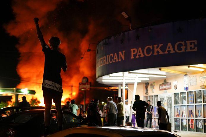 Demonstranten kijken toe terwijl het restaurant waar het incident plaatsvond in vlammen opgaat.