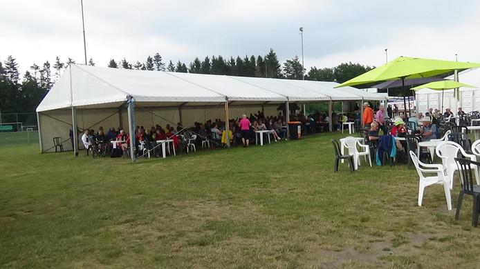 De regen begint te vallen bij de finish van de Vierdaagse Apeldoorn. Mensen zoeken beschutte plekjes op.