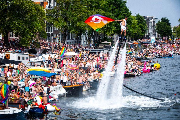 Feestvierende toeschouwers op de Amstel tijdens de botenparade in de grachten vorig jaar. Beeld ANP