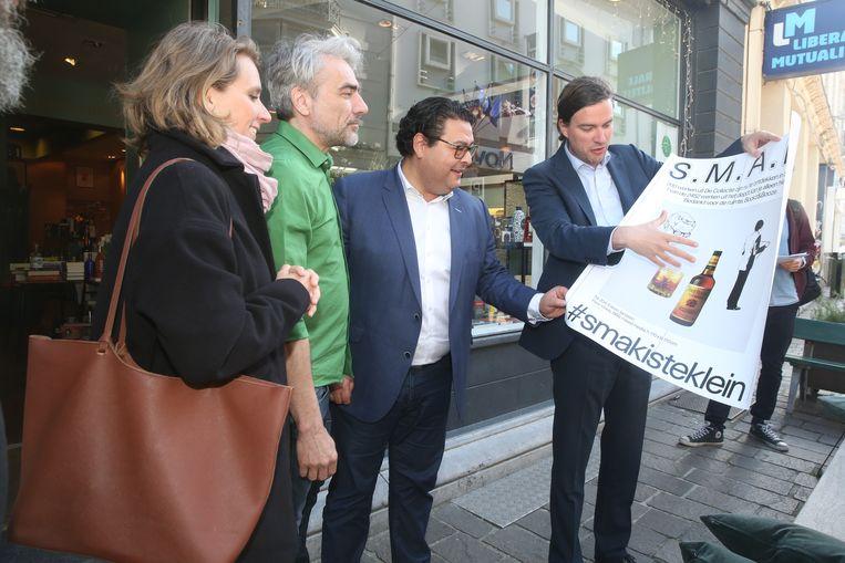 Burgemeester De Clercq en schepen Souguir overhandigen het kunstwerk aan handelaar Ief Stuyvaert.