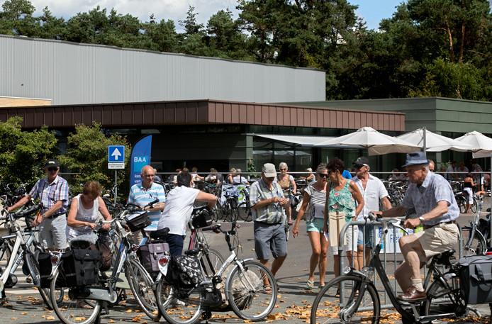 Deelnemers aan de Fietsdriedaagse stappen op de fiets na versnaperingen en drankjes bij Kempenhaeghe in Heeze.