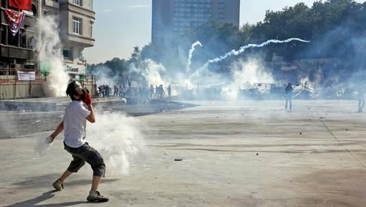 Een demonstrant gooit een kogel met traangas terug naar de politie.
