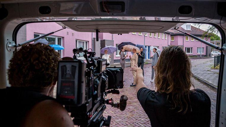 Regisseur Robin de Puy instrueert de modellen vanuit het busje. Links cameraman Maarten van Rossem. Beeld Rink Hof