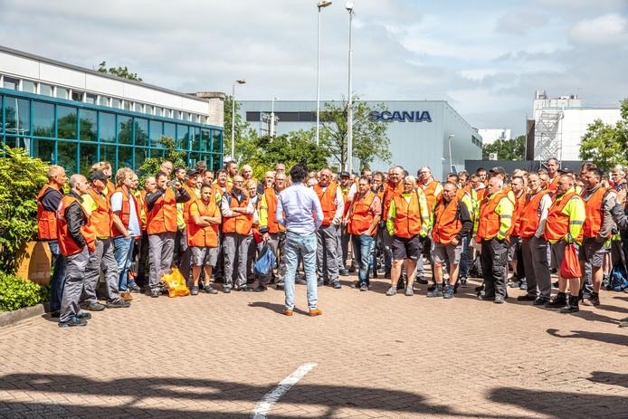 Werknemers van Scania luisteren naar vakbondsman Marijn van der Gaag van FNV.