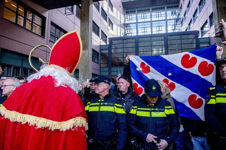 Een sympathisant van de 'blokkeerfriezen' mocht verkleed als Sinterklaas de zitting in Leeuwarden niet bijwonen. Andere sympathisanten zwaaien met de Friese vlag.